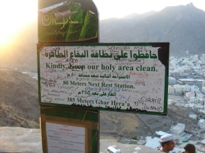 "A sign reads: ""Kindly keep our hold area clean."" The sign is severely defaced, with grafitti all over it."