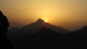 The infant sun peeks out from behind a mountain peak