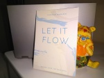 """An painted statue of WInnie the Pooh behind a book titled """"Let it Flow"""""""
